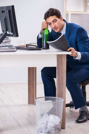 Young businessman employee drinking in the office at desk Stock Photo