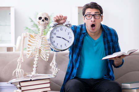 Student studying with skeleton preparing for exams 스톡 콘텐츠
