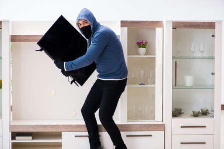 Man burglar stealing tv set from house Stock Photo