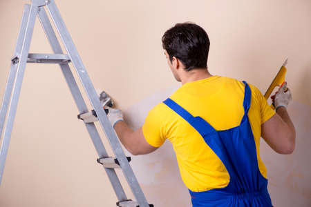 Young contractor employee applying plaster on wall Stok Fotoğraf