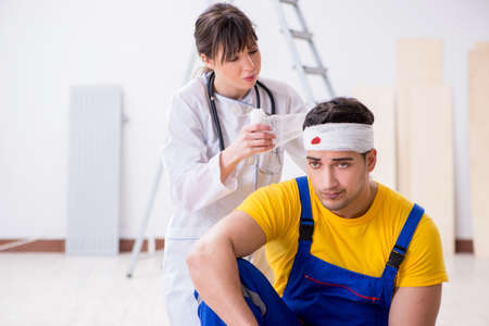 Worker with injured head and doctor Stock Photo