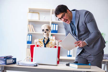 Angry boss yelling at his skeleton employee Stock Photo