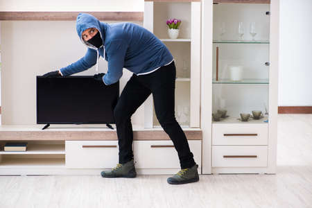 Man burglar stealing tv set from house Imagens