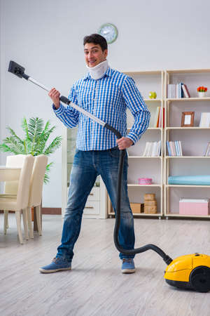 Injured man with neck injury vacuum cleaning house Stock Photo