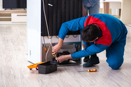 Man repairing fridge with customer Stock Photo