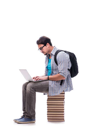 Young student sitting on top of book stack on white Foto de archivo
