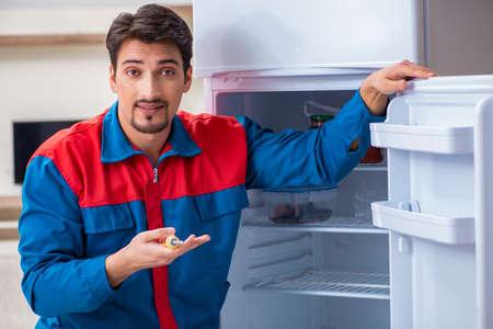 Professional contractor repairing broken fridge Stockfoto