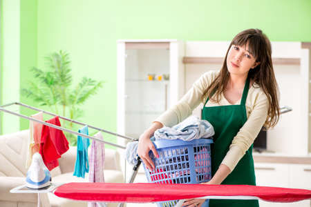 Young woman ironing clothing at home 免版税图像