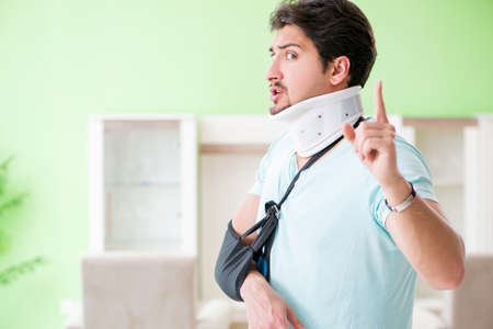 Young student man with neck and hand injury at home Foto de archivo - 104779698