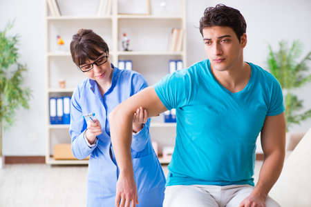 Doctor checking nerve reflexes with hammer Stock Photo