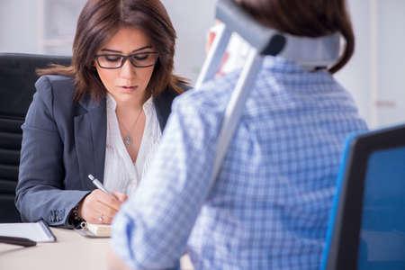 Gewonde werknemer bezoekt advocaat voor advies over verzekeringen Stockfoto