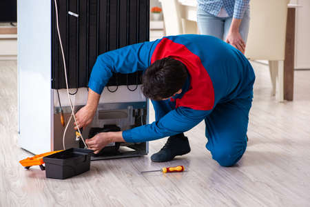 顧客と冷蔵庫を修理する男 写真素材 - 104829921