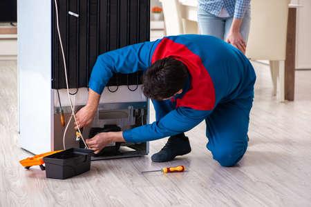 Uomo che ripara il frigorifero con il cliente Archivio Fotografico