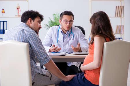 Mujer embarazada con su marido visitando al médico en la clínica