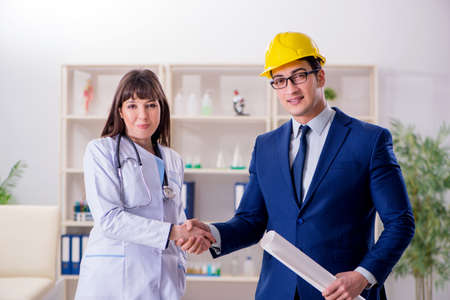 Doctor discussing new hospital plan with architect