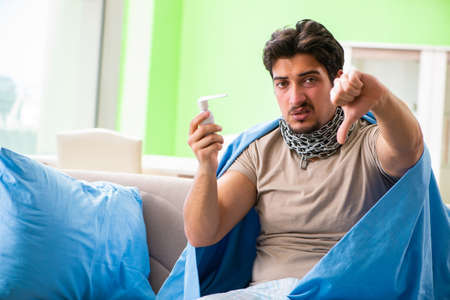Sick young man suffering from flu at home Stock Photo