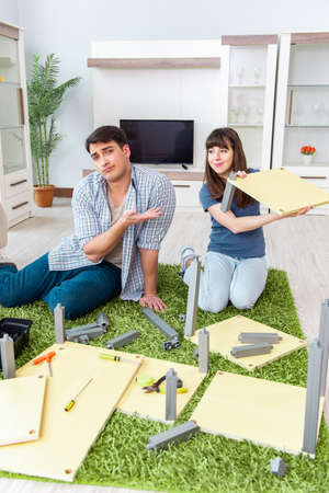 Young family assembling furniture at new house 版權商用圖片