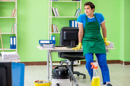 Handsome man cleaning office with vacuum cleaner