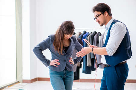 Professional tailor taking measurements for formal suit