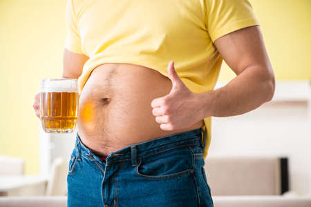 Fat obese man holding beer in dieting concept