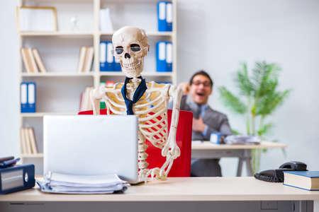 Uomo d'affari che lavora con lo scheletro in ufficio