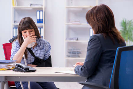 Injured employee visiting lawyer for advice on insurance Stock Photo