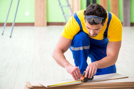 Professional contractor laying flooring at home Banco de Imagens