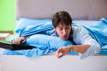 Employee in the bedroom being late for his job Stock Photo