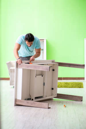 Man repairing furniture at home 免版税图像