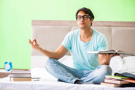 Student preparing for exams at home in bedroom sitting on the be