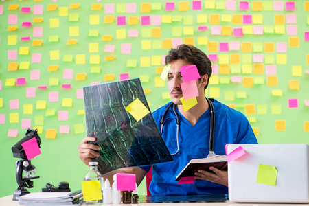 Young doctor with many reminders and urgent work Stock Photo