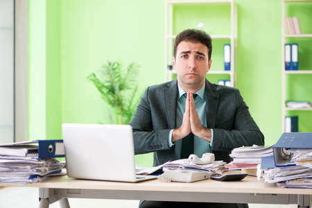 Businessman angry with excessive work sitting in the office