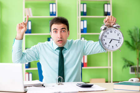 Male financial manager working in the office in time management