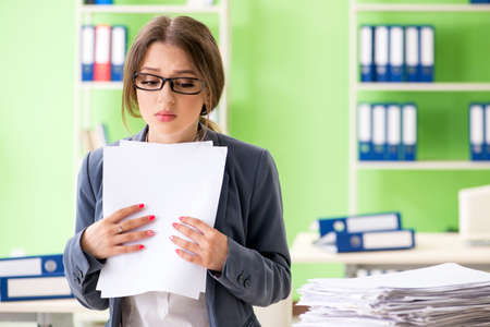 Young female employee very busy with ongoing paperwork 版權商用圖片