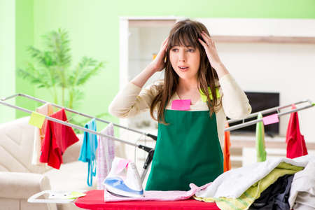 Young woman ironing clothing at home Standard-Bild