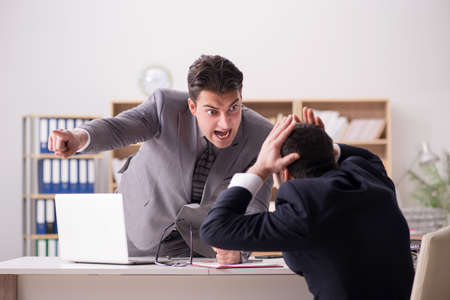 Angry boss shouting at his employee Stock Photo