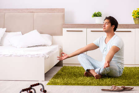 Young man doing yoga in bedroom Stock Photo