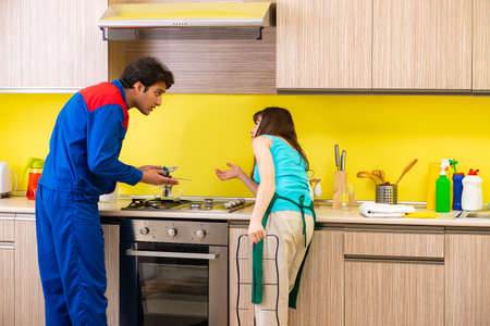 Woman with contractor at kitchen discussing repair Stock fotó