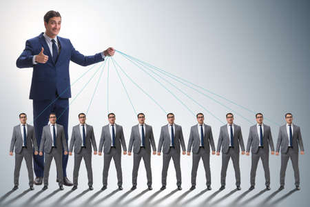 Boss employee manipulating his staff in business concept Stockfoto