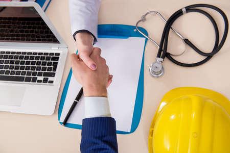 Médico y gerente acuerdan la cobertura del seguro industrial Foto de archivo