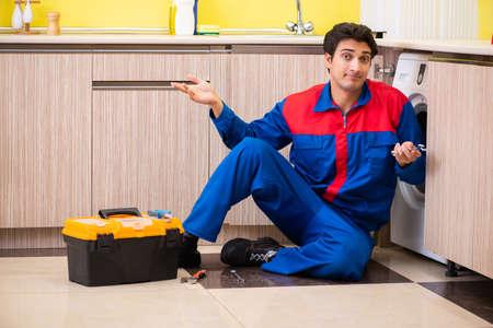 Repairman repairing washing machine in the kitchen Stock Photo