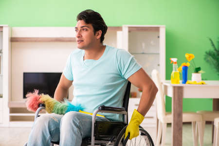 Disabled man on wheelchair cleaning house Standard-Bild