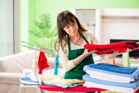 Młoda kobieta prasowanie odzieży w domu