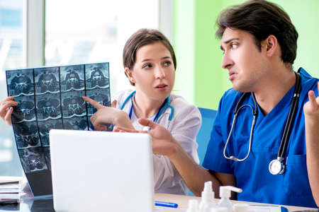 Woman and man gynecologists discussing medical case at the clinic