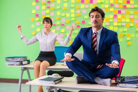 Homme et femme au bureau avec de nombreuses priorités conflictuelles Banque d'images