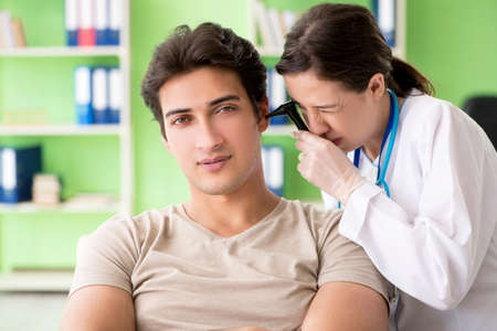 Female doctor checking patients ear during medical examination