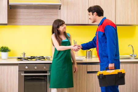 Woman with contractor at kitchen discussing repair Stock Photo