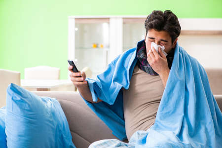Sick young man suffering from flu at home 版權商用圖片