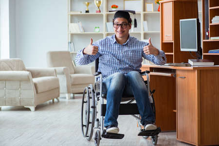 Disabled student studying at home on wheelchair Фото со стока