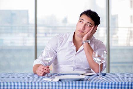 Handsome man alone in restaraunt on date Stock Photo